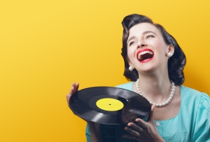 Happy woman with a vinyl record in her hands