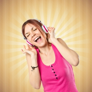 Young girl listening music over pop background