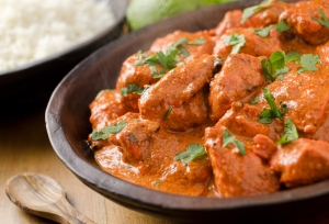 A delicious bowl of creamy butter chicken with basmati rice and cilantro.